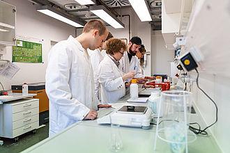 Studierende beim Experimentieren im Laborbank
